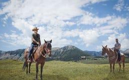 Två män varje sammanträde på en häst med majestätiska berg i bakgrunden Royaltyfri Foto