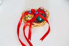 Två målade ägg med det onda ögat på en korg med röda band Royaltyfri Bild