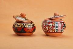 Två målade den handgjorda keramiska krukan med lock på kraft papper Royaltyfria Foton