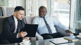 Två mång--person som tillhör en etnisk minoritet affärsmän som ser skrivplattan och diskuterar startprojekt i glas- kafé under lu stock video