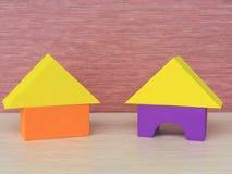 Två mångfärgade gula, purpurfärgade orange hus av byggnadskvarter triangel, rektangel, en bildande leksak för barn på en rosa bac arkivbilder