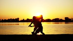 Två mörkermandiagram, på soluppgång, mot ljuset, boxning, stridighet, i att munhuggas som utbildar i ett par av tekniker av stock video