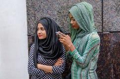 Två maldivian flickor för muslim på gatan genom att använda mobiltelefonen royaltyfri bild