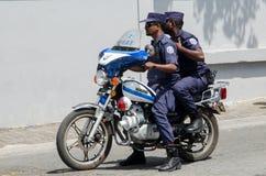 Två maldivian poliser som rider på mopeden på gatan Royaltyfri Bild
