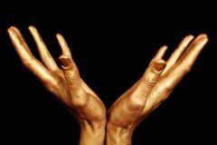 Två male händer i isolerad guldmålarfärg Arkivfoto