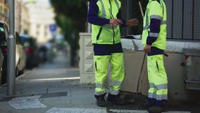 Två manliga anställda av tjänste- meddela för kommunal stad under avbrottet, jobb arkivfilmer