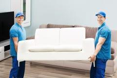 Två manliga arbetare som bär soffan Arkivfoton