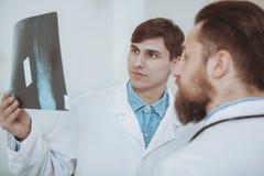 Två manliga doktorer som diskuterar röntgenstrålebildläsningar på sjukhuset royaltyfri bild