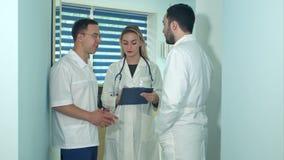 Två manliga doktorer som har diskussion medan kvinnliga sjuksköterskadanandeanmärkningar arkivfilmer
