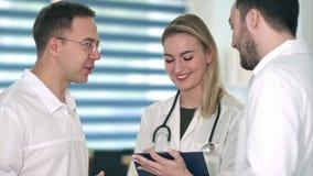 Två manliga doktorer som har diskussion, medan le sjuksköterskadanandeanmärkningar i hennes skrivplatta arkivfilmer