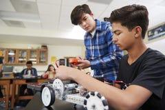 Två manliga elever som bygger det Robotic medlet i vetenskapskurs royaltyfri foto