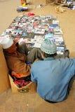 Två manliga försäljare som sitter på ett golv och säljer gods på marknaden i Tripoli, Libia arkivfoton