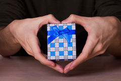Två manliga händer i form av asken för gåva för hjärtainnehavblått den rutiga Arkivfoto