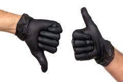 Två manliga händer i svarta handskar visar gester med deras tummar u fotografering för bildbyråer