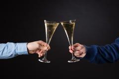 Två manliga händer som rymmer champagneexponeringsglas Royaltyfri Foto