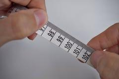 Två manliga händer som rymmer en måttband som mäter längd i cm och meter Royaltyfri Foto
