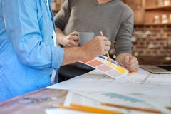 Två manliga kollegor som väljer en färg under kaffeavbrott Arkivbilder