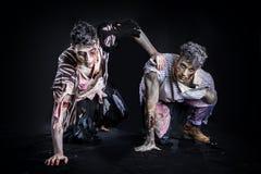 Två manliga levande död som kryper på deras knä, på svart Royaltyfri Fotografi