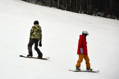 Två manliga snowboarders med bräden som står på det snöig sluttande i Bukovel Arkivbilder