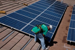 Två manliga sol- arbetare installerar solpaneler Fotografering för Bildbyråer