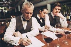 Två manliga sommeliers och den kvinnliga sommelieren utgör sammanträde för vinlista på tabellen med exponeringsglas av vin fotografering för bildbyråer
