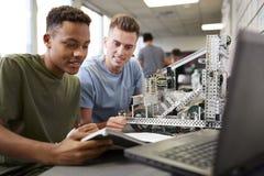 Två manliga universitetsstudenter som bygger maskinen i vetenskapsrobotteknik eller iscensätter grupp royaltyfria bilder