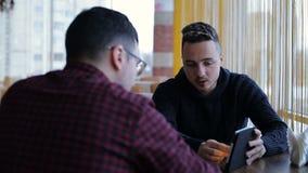 Två manliga vänner med minnestavladatoren som talar i kafé stock video
