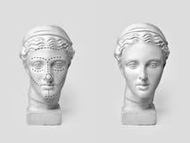 Två marmorhuvud av unga kvinnor, gammalgrekiskagudinnabyst som after markeras med linjer för plastikkirurgi, och skulptur Arkivbilder