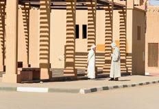 Två marockanska män i den vita djellabaen talar på gatan i den Merzouga byn, Marocko Arkivfoton