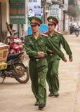 Två marschera soldater i gatan av den lantliga staden. Royaltyfri Bild