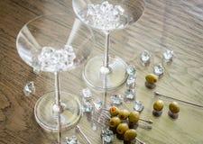 Två martini exponeringsglas med oliv på martini hackor Arkivfoton
