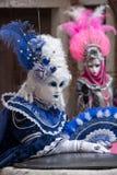 Två maskeringar i dräkt med fans och utsmyckade målade befjädrade maskeringar på den Venedig karnevalet Royaltyfria Foton