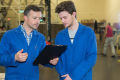 Två mekaniker i fabrik royaltyfri foto