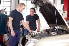 Två mekaniker som arbetar på en bil Royaltyfria Bilder