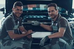 Två mekaniker som sitter nära bilen i garage royaltyfria foton
