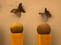 Två metallfjärilar på väggen Arkivfoton