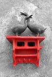 Två metallgäss på en trästol fäste till väggen Royaltyfri Foto