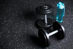 Två metallhantlar och en blå flaska för vatten, utrustning för en idrottshall på en mörk suddig bakgrund arkivbilder
