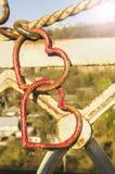 Två metalliska hjärtor som göras av armaturen, förbinds royaltyfria foton