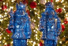 Två metallnötknäpparekritiska anmärkningar framme av en tänd julgran royaltyfri bild