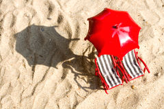 Två miniatyrsolstolar på stranden med paraplyet Royaltyfri Fotografi