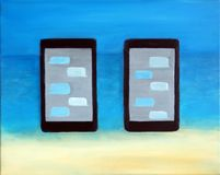 Två mobiltelefoner på en strand Arkivbilder
