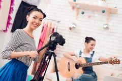Två modebloggerflickor spelar gitarren med en flicka bak kamera royaltyfri foto