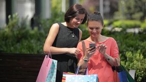 Två modeflickor med påsar som shoppar med en smart telefon i gatan, härlig kvinna som använder telefonen arkivfilmer