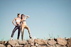 Två modeflickor mot den blåa skyen Royaltyfri Foto