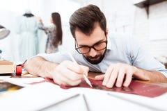 Två modeformgivare som gör utklipp på läder royaltyfri foto