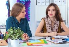 Två modeformgivare som tillsammans arbetar på skrivbordet Arkivbild