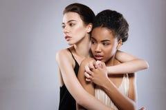 Två modeller av olik bakgrund som tillsammans poserar Royaltyfria Foton