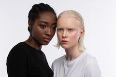 Två modeller med olik hudfärg som poserar för mångfaldartikel royaltyfri fotografi