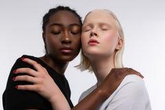 Två modeller som poserar för artikel om mångfald och anti--rasism royaltyfri foto